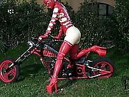 Freaky Babe In Red Latex Bondage Gear Fucks Herself On A Bike